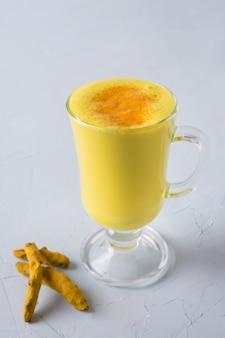 Verre de lait latte au curcuma doré ayurvédique, poudre de curcuma sur blanc.