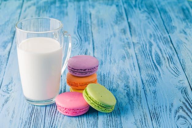 Verre de lait avec macaron français sur table bleue