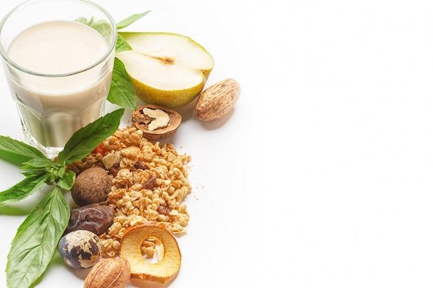 Un verre de lait et de muesli avec des fruits et des herbes sur un fond blanc