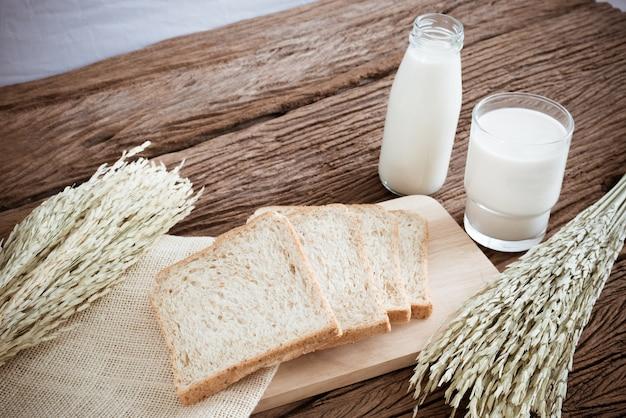 Verre de lait et de pain de blé entier sur la planche de bois