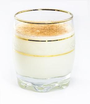 Verre de lait de poule chaud, boisson de noël, à base d'œufs, cannelle, amandes et liqueur de rhum. fond blanc isolé et espace de copie.