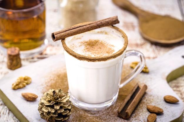Verre de lait de poule préparé avec liqueur, cannelle, sucre raffiné, crème d'amande et rhum, boisson chaude de fin d'année