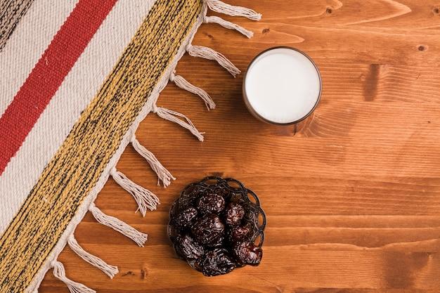 Verre de lait près de soucoupe avec pruneaux et tapis
