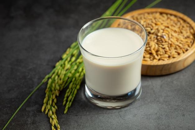 Verre de lait de riz avec plant de riz et graines de riz mis sur un sol sombre