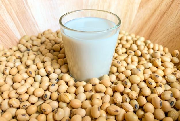Le verre de lait de soja est placé sur beaucoup de tas de soja