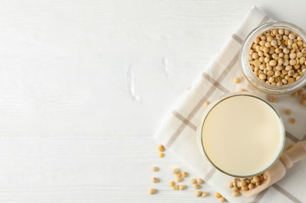 Verre de lait de soja, graines de soja, serviette sur blanc, bois, espace pour le texte. vue de dessus