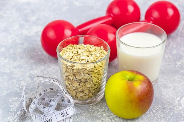 Un verre de lait et un verre de flocons d'avoine (flocons d'avoine). apple avec ruban à mesurer et haltères.