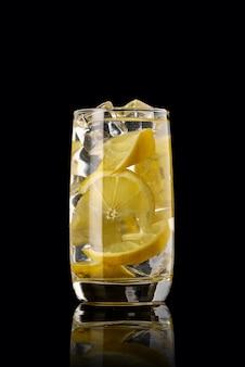Un verre de limonade au citron sur fond noir