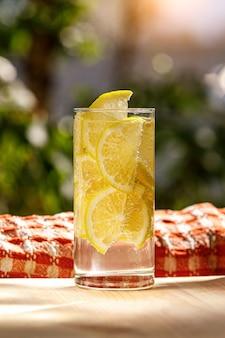 Verre de limonade au citron sur jardin ensoleillé.