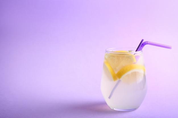Verre de limonade fraîche sur fond de couleur
