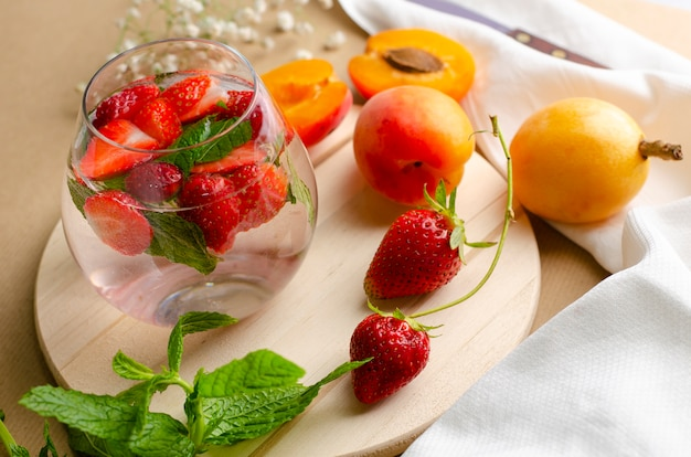 Verre de limonade à la fraise avec des morceaux de fraise et de menthe fraîche