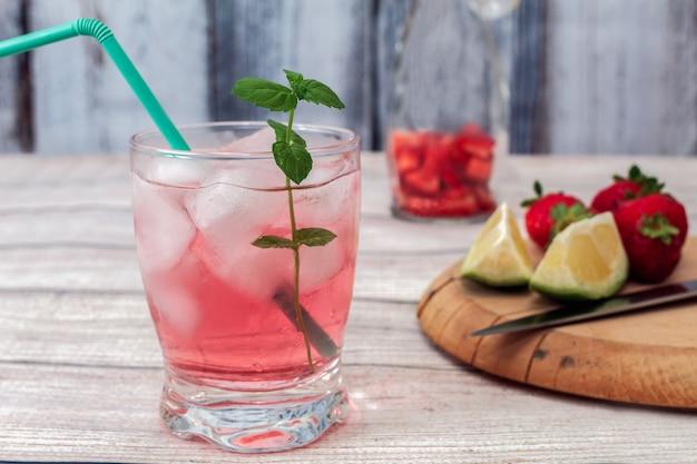 Un verre de limonade rose avec de la glace et un brin de menthe