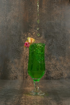 Un verre de limonade verte juteuse et de roses sur une surface en marbre.