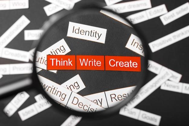 Verre loupe sur l'inscription rouge pensez, écrivez, créez une découpe de papier. entouré d'autres inscriptions sur fond sombre. concept de nuage de mots.