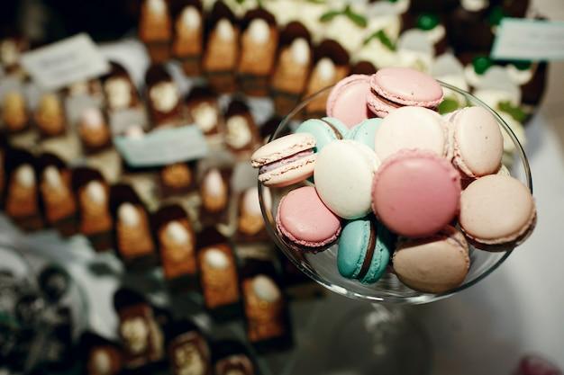 Verre avec des macarons se dresse sur les plaques avec des gâteaux