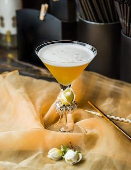 Verre à martini avec des roses et de la mousse.