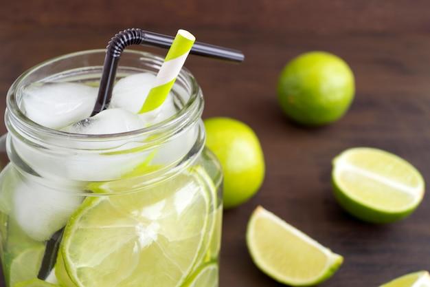 Verre mason de limonade au citron vert et paille sur image de fond en bois