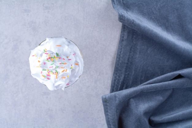 Un verre de milkshake avec de la crème saupoudrée de sucre à côté d'un morceau de tissu, sur le marbre.