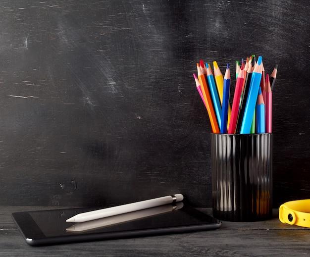 Verre noir avec des crayons de bois multicolores