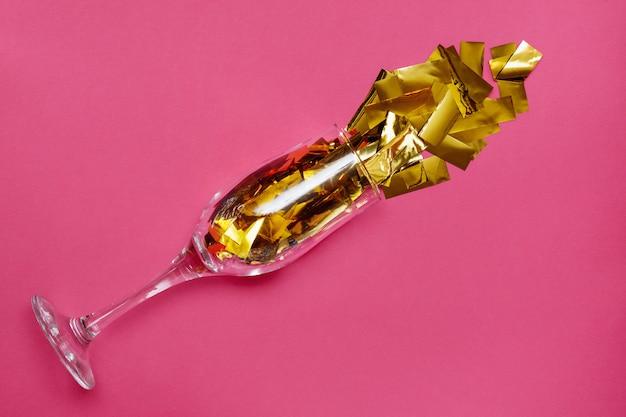 Verre avec de l'or scintille sur un rose
