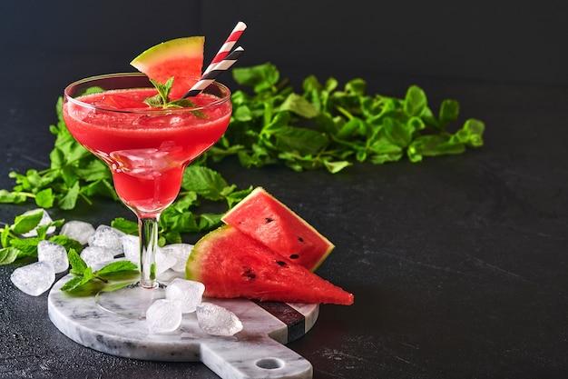 Verre de pastèque margarita cocktail à la menthe et de la glace. boissons rafraîchissantes d'été dans des verres sur tableau noir. concept d'une alimentation saine en été.