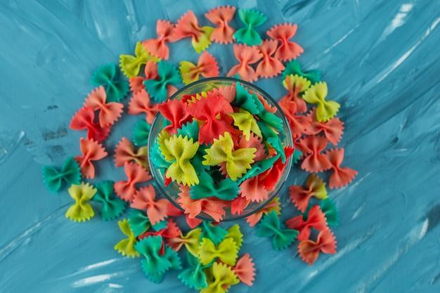 Verre de pâtes farfalle crues colorées sur surface bleue