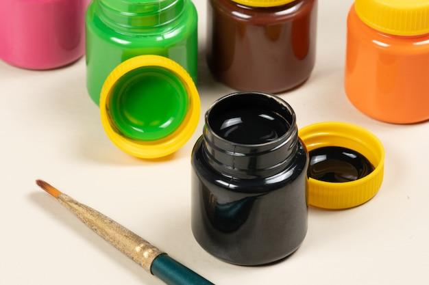 Verre de peinture gouache ouvert avec d'autres tubes en arrière-plan