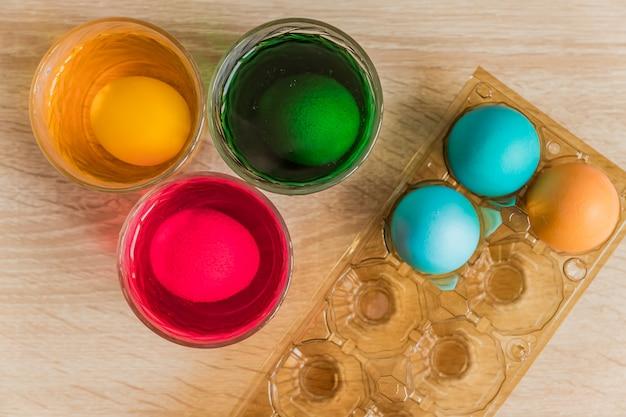 Verre avec peinture orange, rouge et verte pour les oeufs de pâques. décoration d'oeufs de pâques.