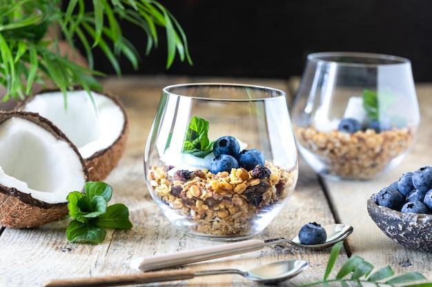 Un verre de petit-déjeuner sain: granola aux bleuets frais, copeaux de noix de coco et menthe