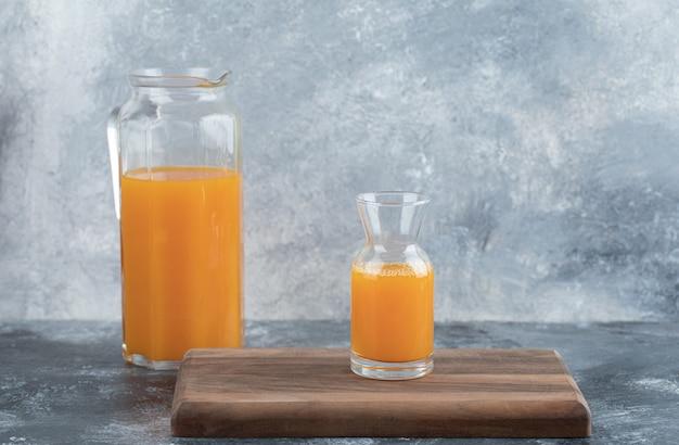 Verre et pichet de jus d'orange sur planche de bois.