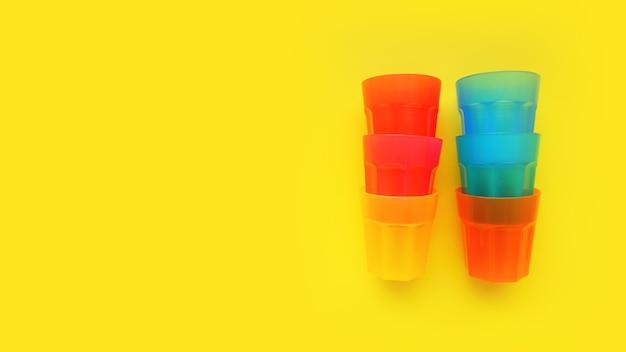 Verre en plastique de différentes couleurs isolé sur une surface jaune - concept d'été lumineux pour la conception et les bannières