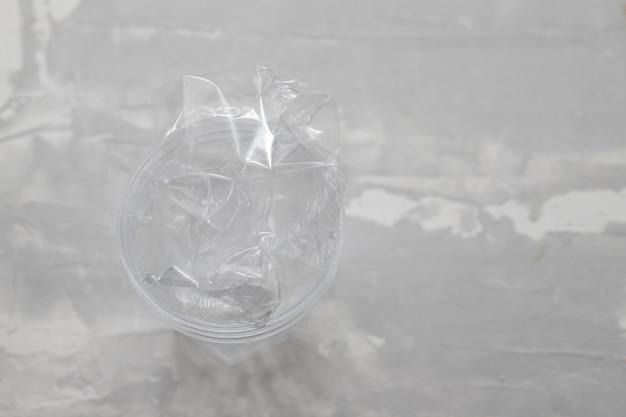 Verre en plastique avec du plastique sur fond en céramique