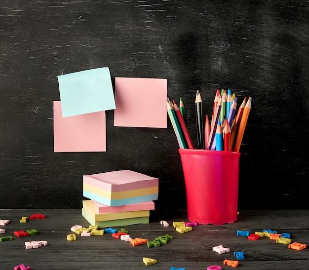 Verre en plastique rouge avec des crayons en bois colorés