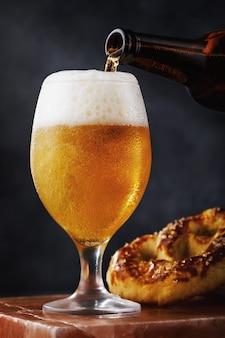 Verre plein de bière légère fraîche avec un bretzel sur un support en pierre