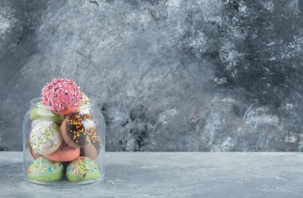 Verre avec plein de biscuits sur table en marbre.