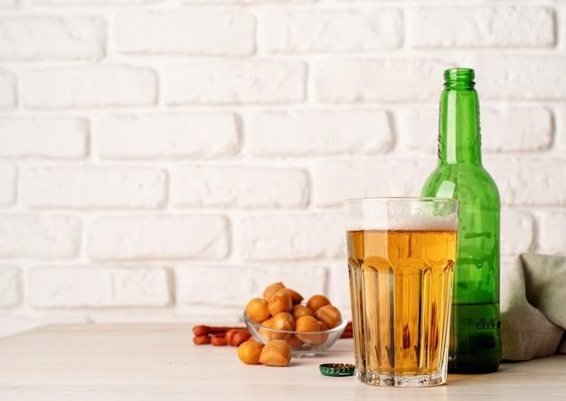 Verre plein de bouteille de bière et de collations fond de mur de briques blanches