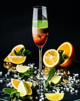 Verre plein de cocktail de lait de poule décoré d'orange au comptoir de bar lumineux.