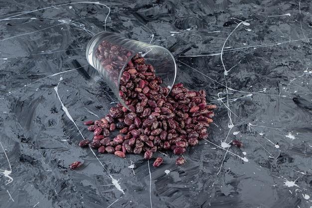 Verre plein de haricots crus placés sur une table en pierre.