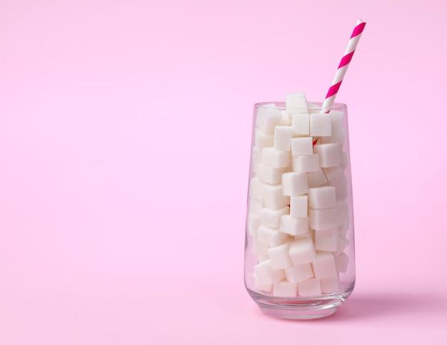 Verre plein de morceaux de sucre. concept de nourriture malsaine.
