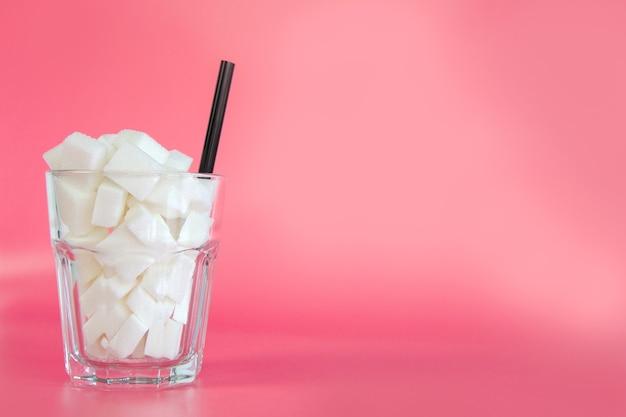 Verre plein de morceaux de sucre avec de la paille sur fond rose et bleu pastel avec espace de copie design rétro sweetscandysodaunhealthy manger concept design moderne coloré