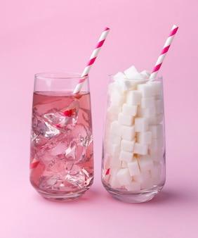 Verre plein de morceaux de sucre et verre d'eau gazeuse. concept de nourriture malsaine.