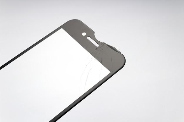 Verre de protection fissuré pour smartphone sur fond blanc.