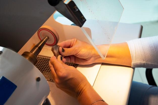 Verre de protection lors du broyage de l'ambre. travail de l'ambre, pierre précieuse entre les mains des femmes, travail de joaillier