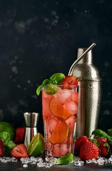 Verre de punch et ingrédients frais pour faire de la limonade, de l'eau détox infusée ou un cocktail. fraises, citron vert, menthe, basilic, glaçons et shaker sur fond noir en pierre ou en béton. mise au point sélective