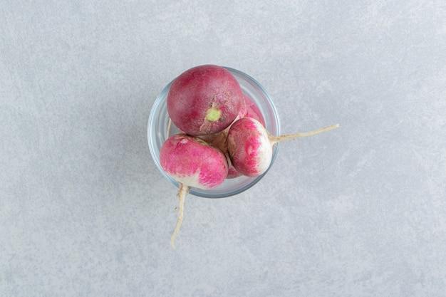 Verre et radis frais, sur fond de marbre.