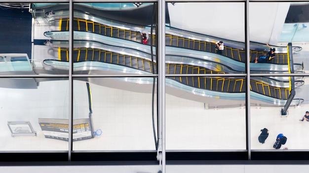 Verre de réflexion des gens vue de dessus marchent et s'asseoir escalator escalier à l'aéroport