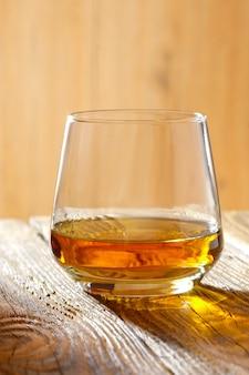Verre renifleur avec du whisky sur une table en bois au soleil