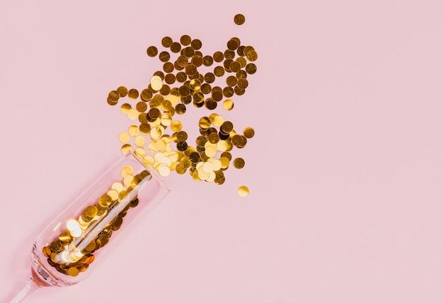 Verre renversant des confettis dorés