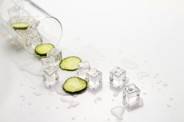 Verre renversé avec de l'eau rafraîchissante, des tranches de concombre et des glaçons.