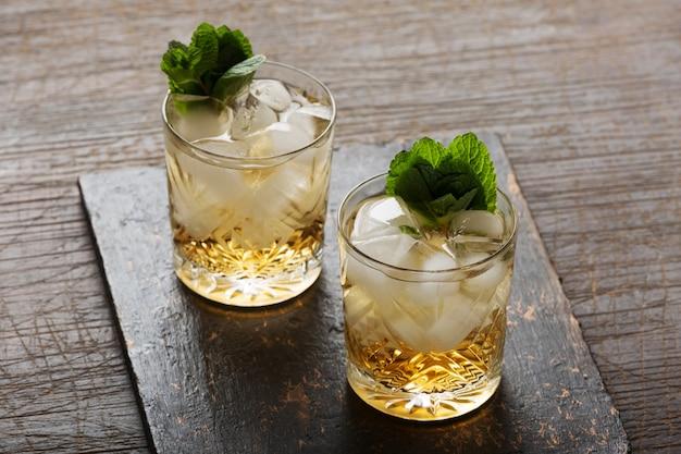 Verre de rhum sur le fond en bois, cuba libre ou cocktail de thé glacé long island avec boissons fortes